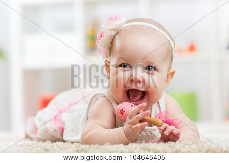 Smiling beautiful child girl lies with toy on carpet