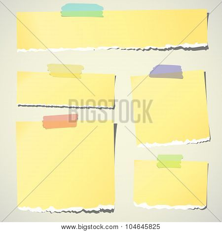 Set of various yellow torn note papers with adhesive tape on background