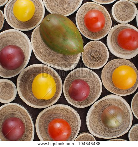 Different colorful whole cherry tomatoes on wood background