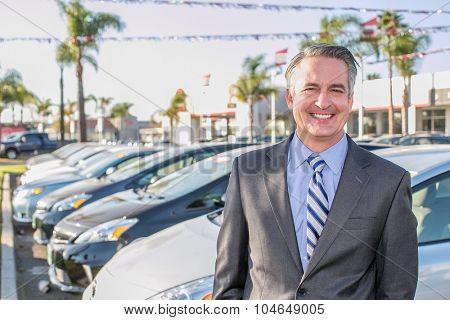 Car salesman standing outside a dealership