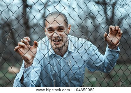 Man Looks Through A Fence Mesh.
