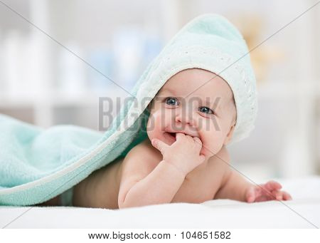 Adorable baby child under towel indoor