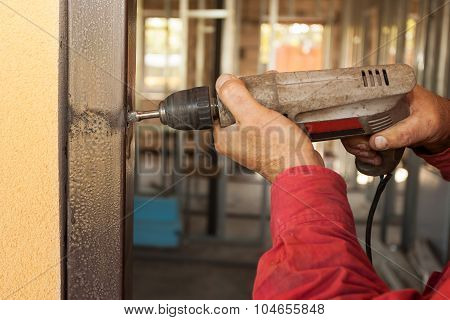 Carpenter at door installation with electric drill