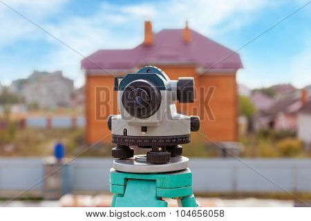 Surveyor equipment optical level or theodolite outdoors at construction site directed on home