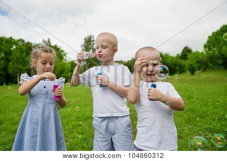 Brothers and sister blowing soap bubbles in park in sunny day