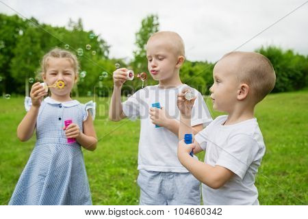 Little brothers and sister blowing bubbles in park on a sunny day