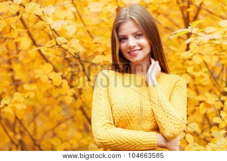 Smiling young woman in autumn forest