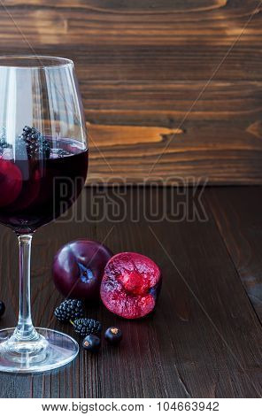 Black sangria with plums and berries. Copy space background