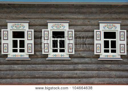 Log Cabin Wall With Three Ornamental Windows