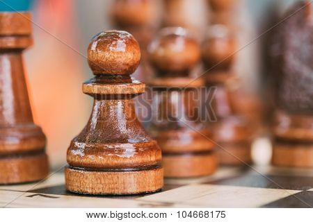 Old Chess Pawn Standing On Wooden Chessboard