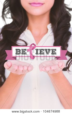Pretty brunette holding out hands against breast cancer awareness message