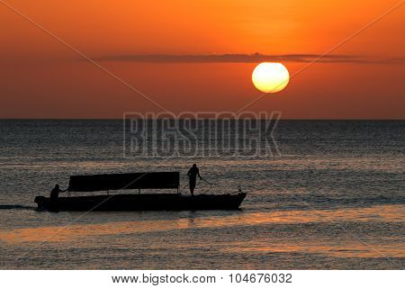 Silhouette of a boat against a golden sunset, Zanzibar island