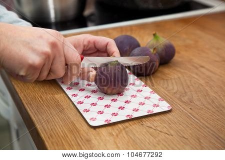 Woman Cutting Fig In Half In The Kitchen