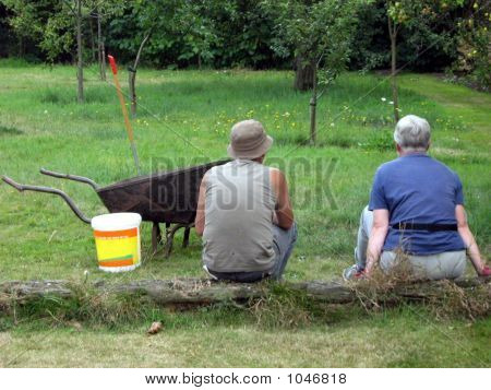 Man And Woman/Gardeners Sitting In Garden/Having Break