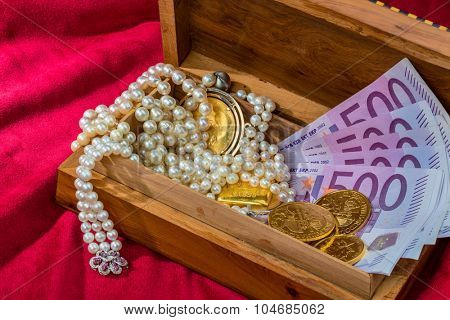 gold in coins and bars with decorations on red velvet. photo icon for wealth, luxury, wealth tax.