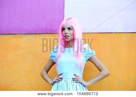 Portrait of beautiful woman with pink hairstyle on bright wall background
