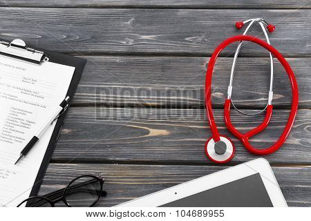 red rubber stethoscope with tablet, glasses and medical history on wooden background