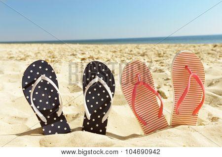 Flip flops on beach sand closeup