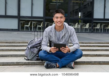 handsome male college student sitting use tablet at campus