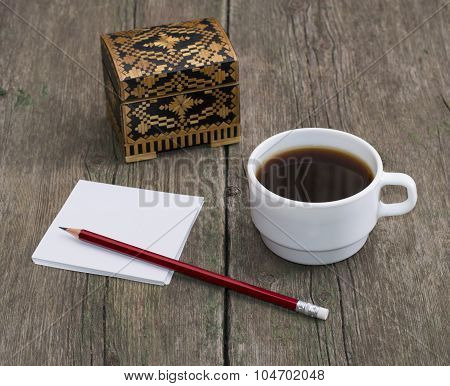 Casket, Coffee In A White Cup And Paper With A Pencil, A Still Life On An Old Table