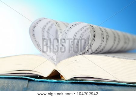 Book pages curved into heart shape on blue background