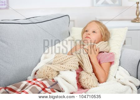 Little girl with sore throat lying on the bed