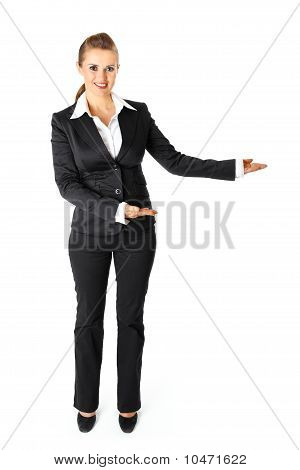 Full length portrait of smiling business woman presenting something on empty hands