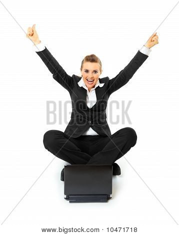 Excited modern business woman sitting on floor and working on laptop