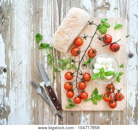 Ciabatta bread with banch of cherry-tomatoes, basil and mozzarella cheese on rustic wooden board ove