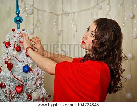 Girl In Red Dress Decorates Christmas Tree.