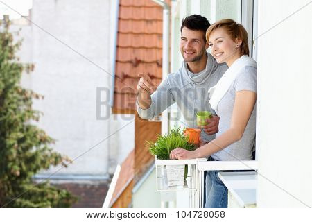 Happy young couple standing at balcony, searching distance, smiling.