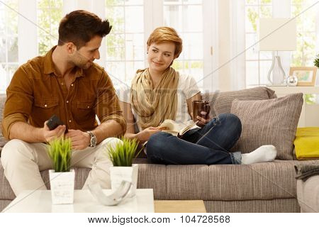 Loving couple sitting at home on sofa, smiling affectionate.