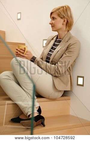 Daydreaming young woman sitting in stairway, drinking tea. Full-length.