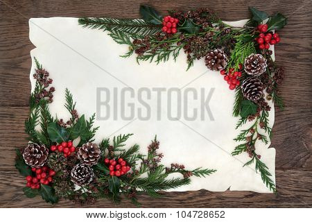 Winter and christmas background border with holly, ivy, pine cones, cedar cypress and fir on parchment paper over old oak wood.