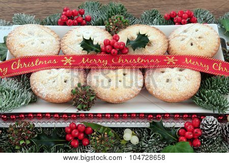 Mince pie cakes on a plate with red merry christmas ribbon, holly, mistletoe and winter greenery.