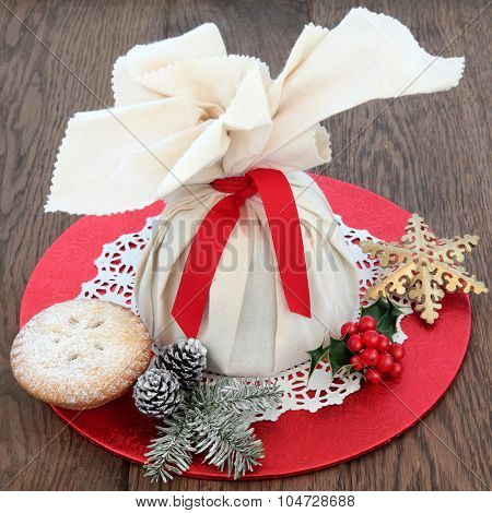 Christmas mince pies with pudding in a muslin bag, holly, winter greenery and snowflake bauble over oak background.