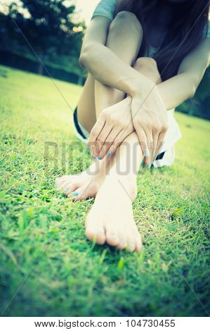Relaxed Asia Young Woman With Bare Feet Sitting On Grass