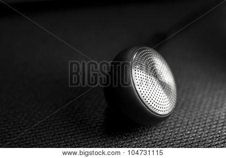 Black ear bud on black background