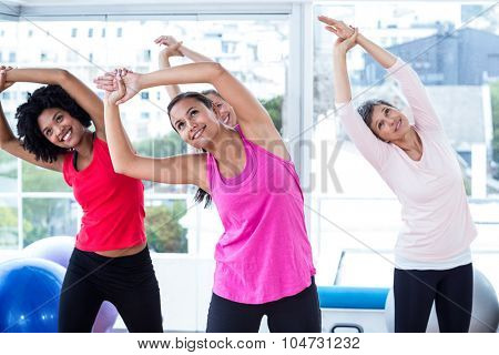 Smiling women exercising with arms raised in fitness studio