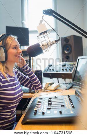 Happy female radio host broadcasting through microphone in studio