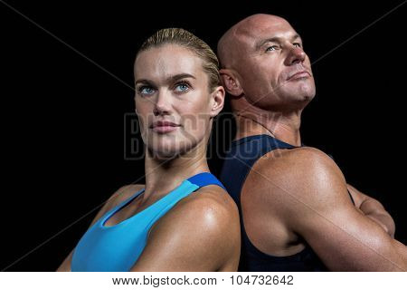 Man and woman standing back to back against black background