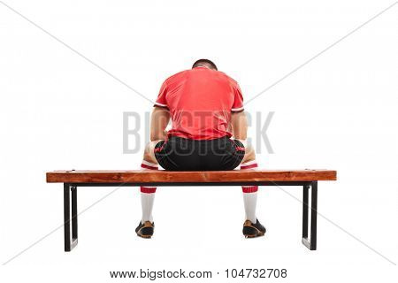 Rear view studio shot of a sad male football player sitting on a wooden bench and looking down isolated on white background