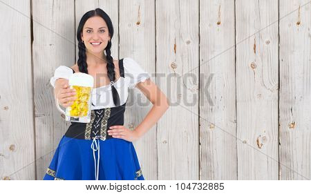 Pretty oktoberfest girl holding beer tankard against wooden background