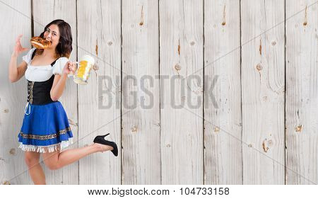 Pretty oktoberfest girl holding beer tankard and pretzel against wooden background