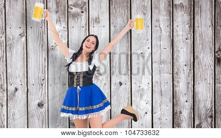 Pretty oktoberfest girl holding beer tankards against digitally generated grey wooden planks
