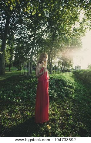 young blonde woman in long red dress hold flower in one hand outdoor shot in park, summer day, full body shot