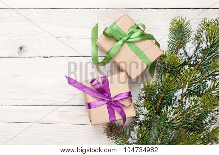 Christmas fir tree with snow and gift boxes on rustic wooden board with copy space