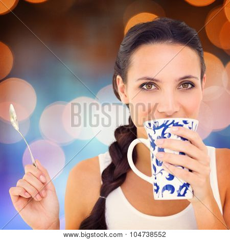 Pretty brunette having cup of tea against glowing background