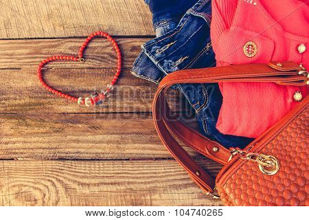 Women's clothing and accessories: sweater, jeans, handbag, beads on wooden background. Toned image.