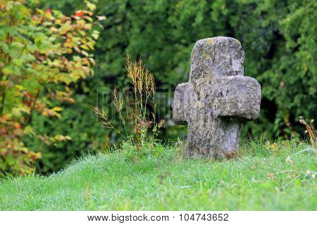 old stone cross in green grass